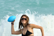 TV Host Maria Menounos wearing a skimpy black Vitamin A bikini on the beach in Miami. Maria had fun splashing around and playing football with Actor Michael Chiklis.
