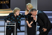(L-R) Betty White, Kate McKinnon, and Alec Baldwin speak onstage during the 70th Emmy Awards at Microsoft Theater on September 17, 2018 in Los Angeles, California.