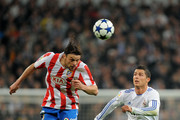 Tomas Ujfalusi (L) of Atletico Madrid heads the ball ahead of Cristiano Ronaldo of Real Madrid during the Copa del Rey quarter final first leg match between Real Madrid and Atletico Madrid at Estadio Santiago Bernabeu on January 13, 2011 in Madrid, Spain.