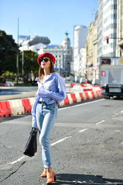 Effortlessly with an oversize button-up and classic blue jeans.