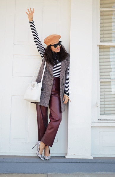 With stripes, a long coat vest and leather pants.